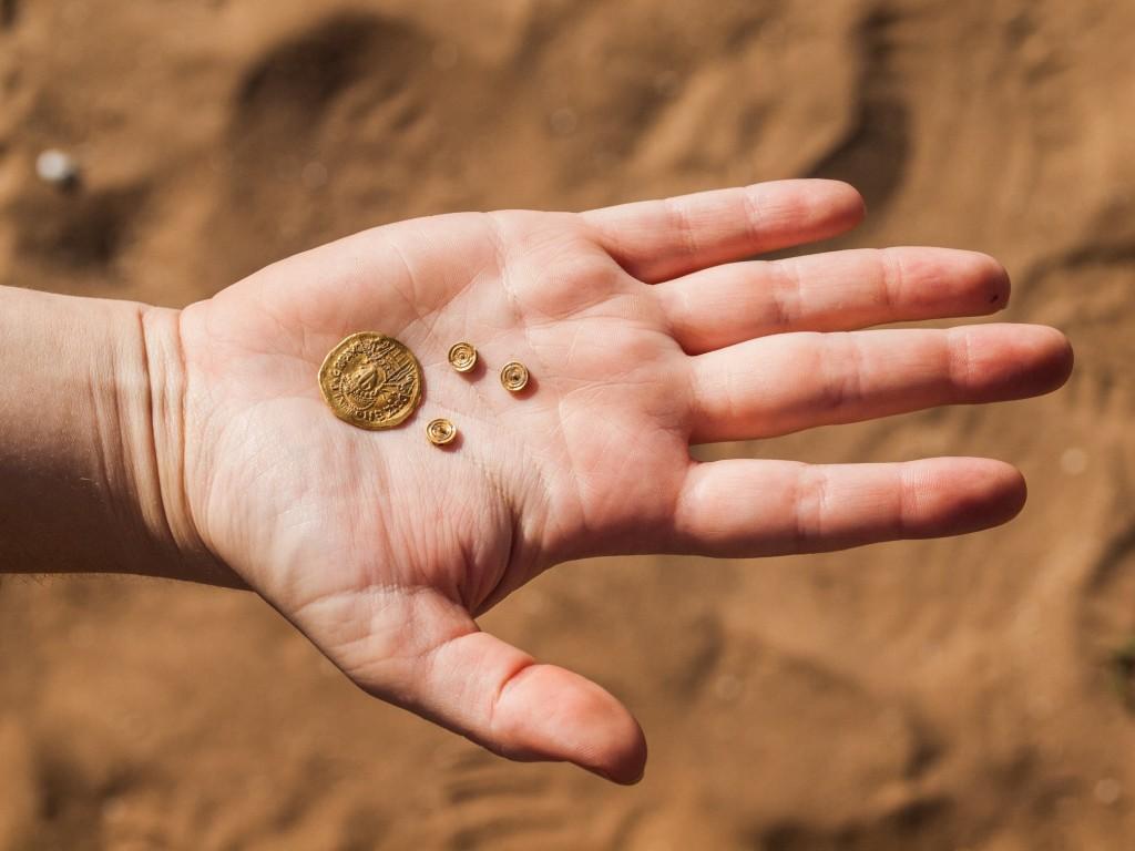 מטבע זהב ושלושה שיבוצים אשר עיטרו תכשיט זהב. צילום: אסף פרץ, באדיבות רשות העתיקות