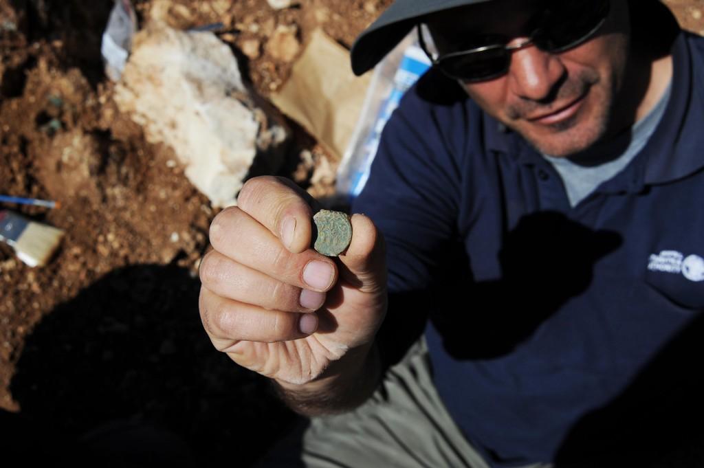 הארכיאולוג פבלו בצר עם אחד ממטבעות המטמון - צילום: ולדימיר נייחין