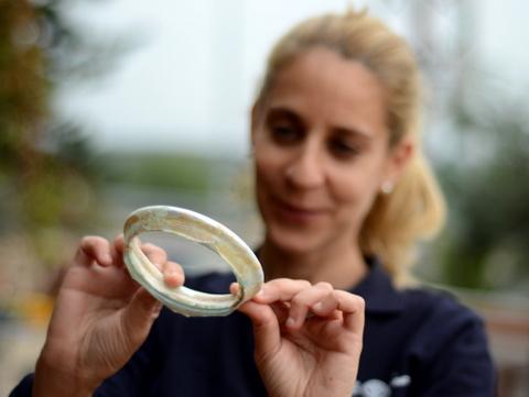הארכאולוגית לימור תלמי מחזיקה בסיס קערת זכוכית - צילום: יולי שוורץ