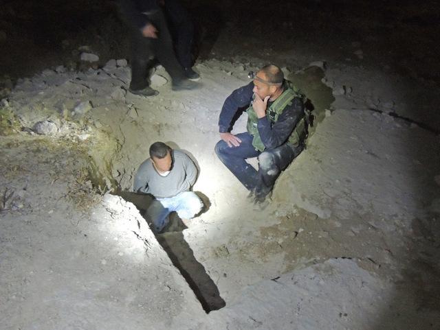 אחד מהחשודים שנתפסו (פניו טושטשו) בכניסה למערה העתיקה - צילום: היחידה למניעת שוד ברשות העתיקות