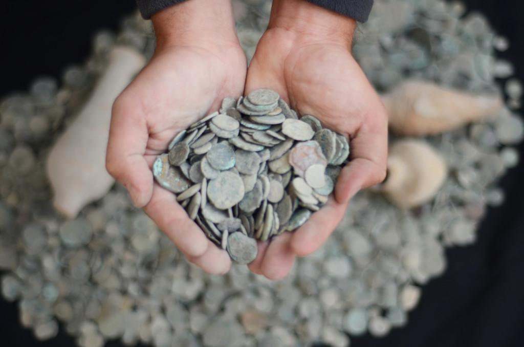 חופן מטבעות מיני רבים שנמצאו אצל האספן הסוחר - צילום: רשות העתיקות