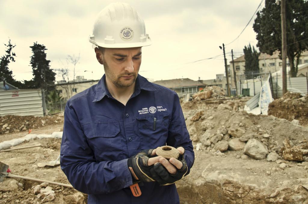 מנהל החפירה, אלכס ויגמן, מחזיק נר מהתקופה הרומית המאוחרת שנמצא באתר. צילום: באדיבות רשות העתיקות