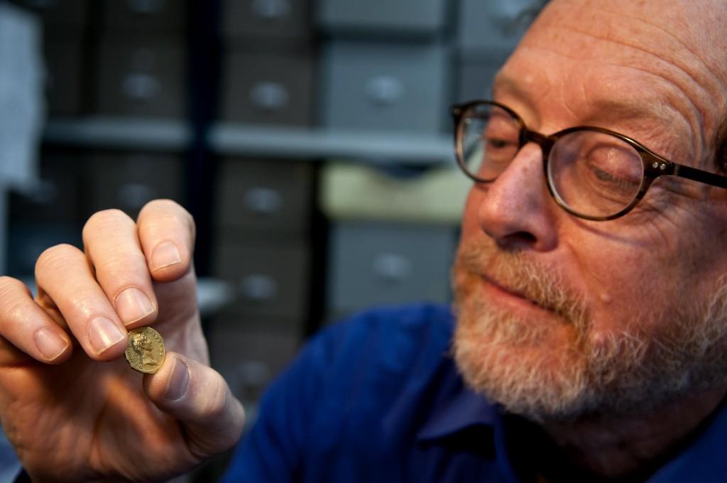 """ד""""ר דונלד צבי אריאל, ראש ענף מטבעות ברשות העתיקות, בוחן את המטבע הנדיר. צילום: שי הלוי, רשות העתיקות"""