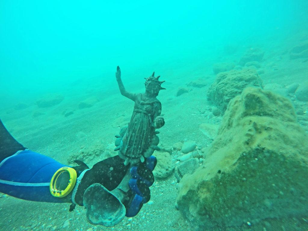 שבר נר ברונזה מעוטר בדמות האל סול כפי שנתגלה בים. צילום: רן פיינשטיין