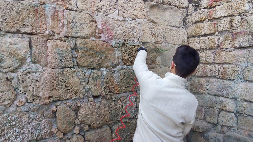 משמר של רשות העתיקות מנקה את קיר המצודה. צילום: אריאל ענבר