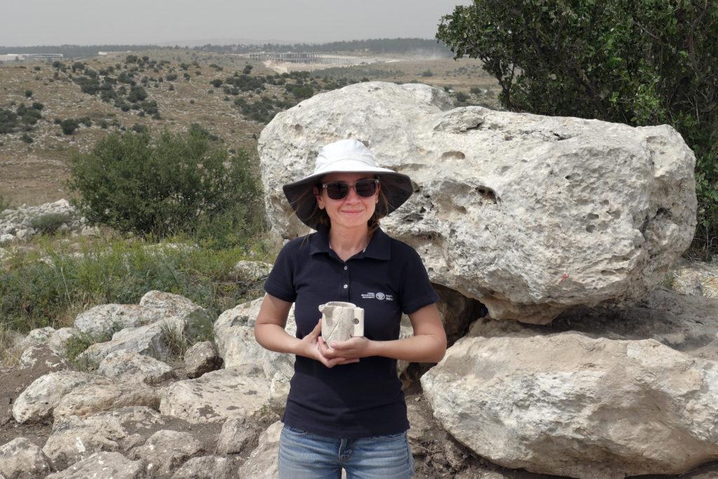 . ארכיאולוגית רשות העתיקות, ג'ני מרכוס, מחזיקה ספל אבן מימי הבית השני שהתגלה בבית האחוזה. צילום: אברהם טנדלר