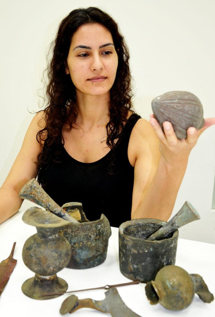 עובדת רשות העתיקות בוחנת את הממצאים. צילום: אמיר גורזלזני
