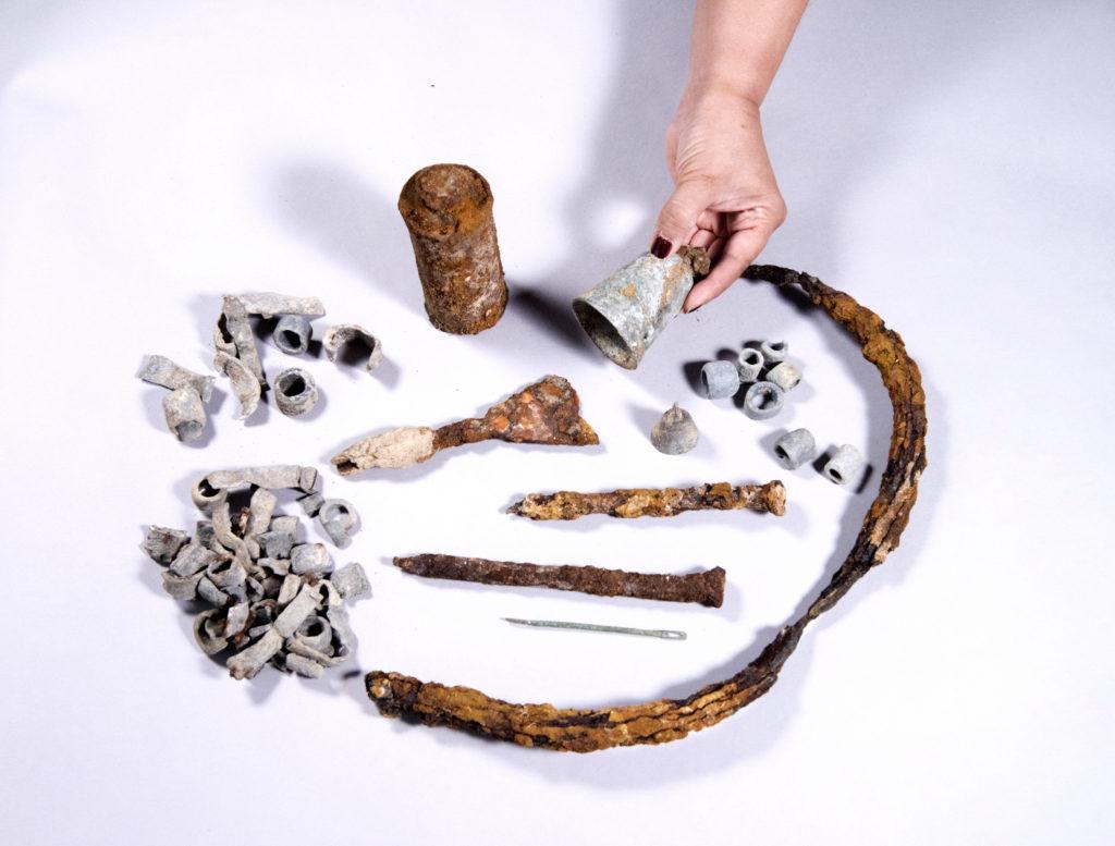 הממצאים שנחשפו בחפירה: קרסים ממתכת, עשרות משקלות עופרת, פעמון גדול מברונזה, ועוד. צילום: קלרה עמית