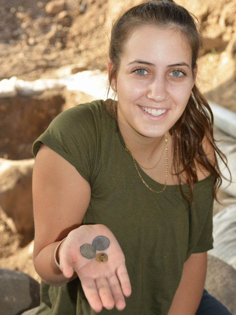 """דור יגב, חניכת מכינת """"גליל עליון"""", עם המטבעות שנחשפו בחפירה. צילום: גלעד צינמון"""