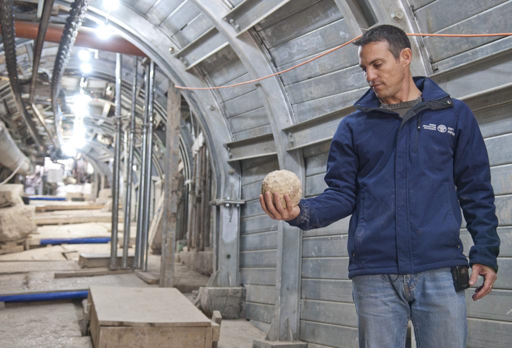 נחשון זנטון מחזיק אבן בליסטרה שככל הנראה שמשה את צבא טיטוס בקרב על כיבוש ירושלים -צלם שי הלוי