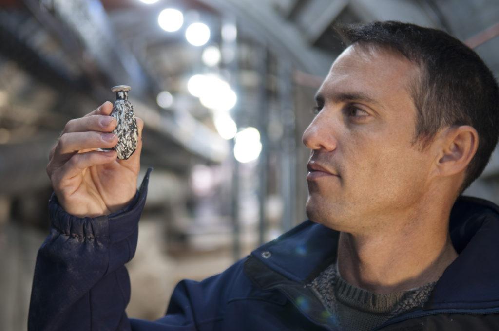 נחשון זנטון מחזיק כלי זכוכית קטן ונדיר בצורת תמר שנחשף בחפירות הרחוב. צילום: שי הלוי