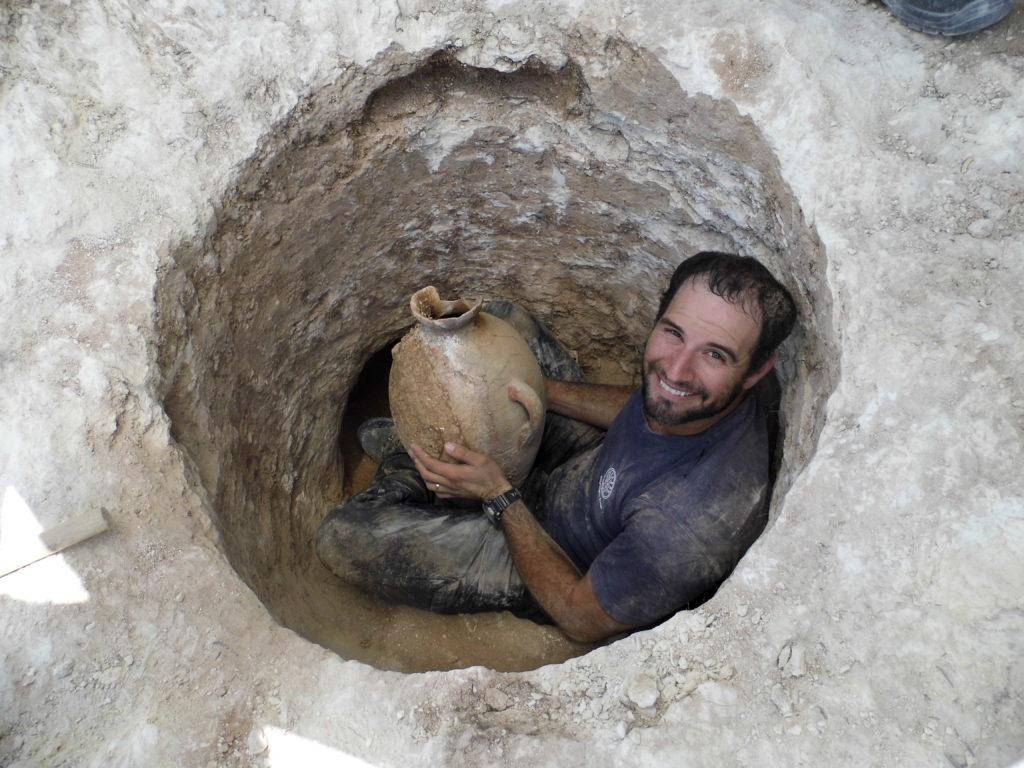 ארכיאולוג רשות העתיקות דוד תנעמי משתחל לפתח הקבר הצר ומוציא החוצה קנקן. צילום: שועה קיסילביץ