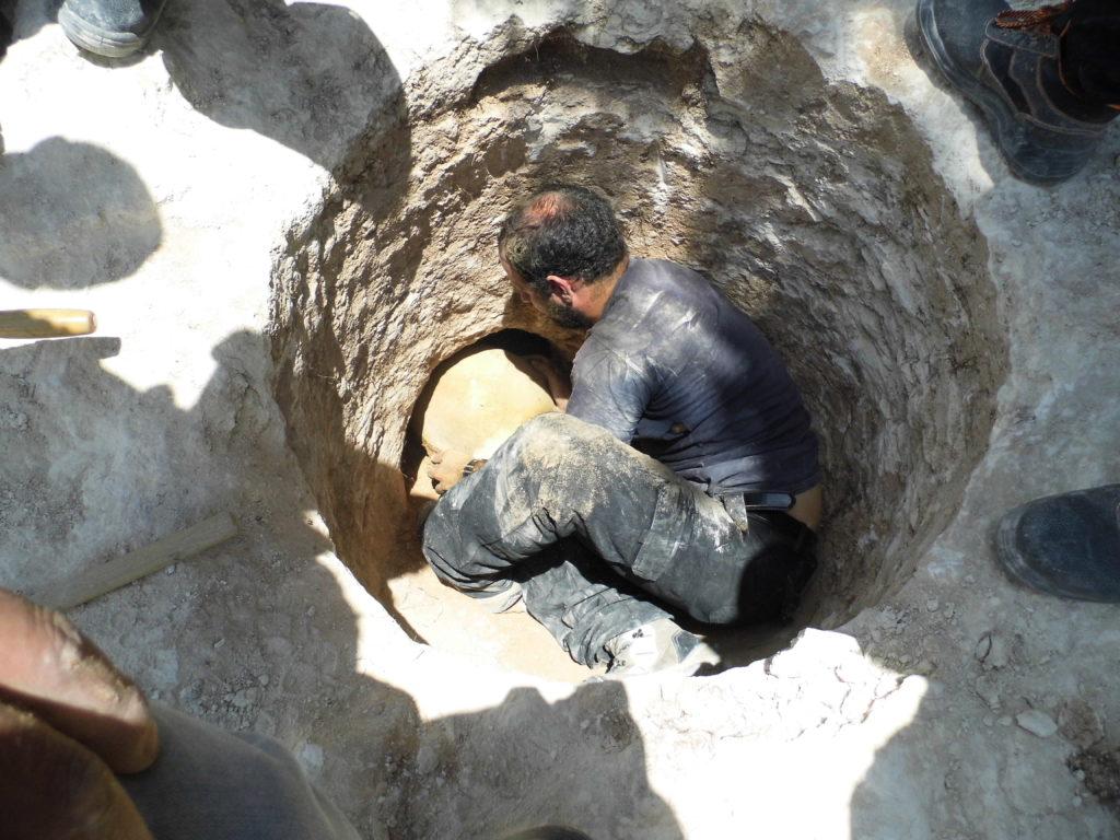ארכיאולוג רשות העתיקות דוד תנעמי משתחל לפתח הקבר הצרומוציא החוצה קנקן. צילום: שועה קיסילביץ