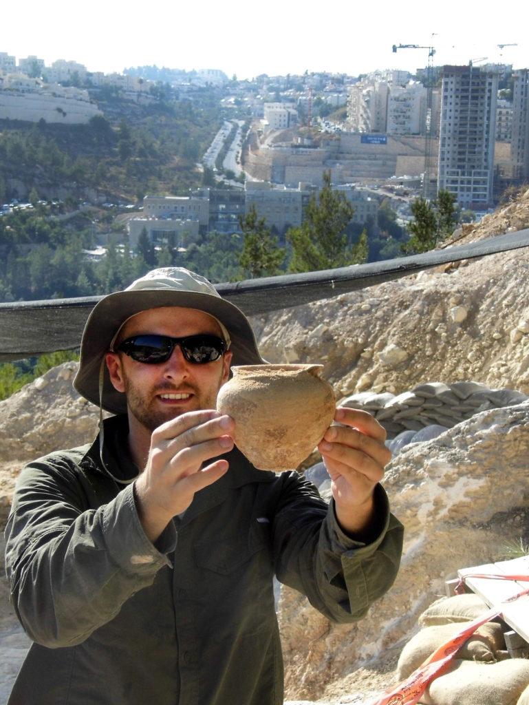 ארכיאולוג רשות העתיקות אלכס ויגמן מציג קערה שהוצאה מהקבר העתיק. צילום: שועה קיסילביץ