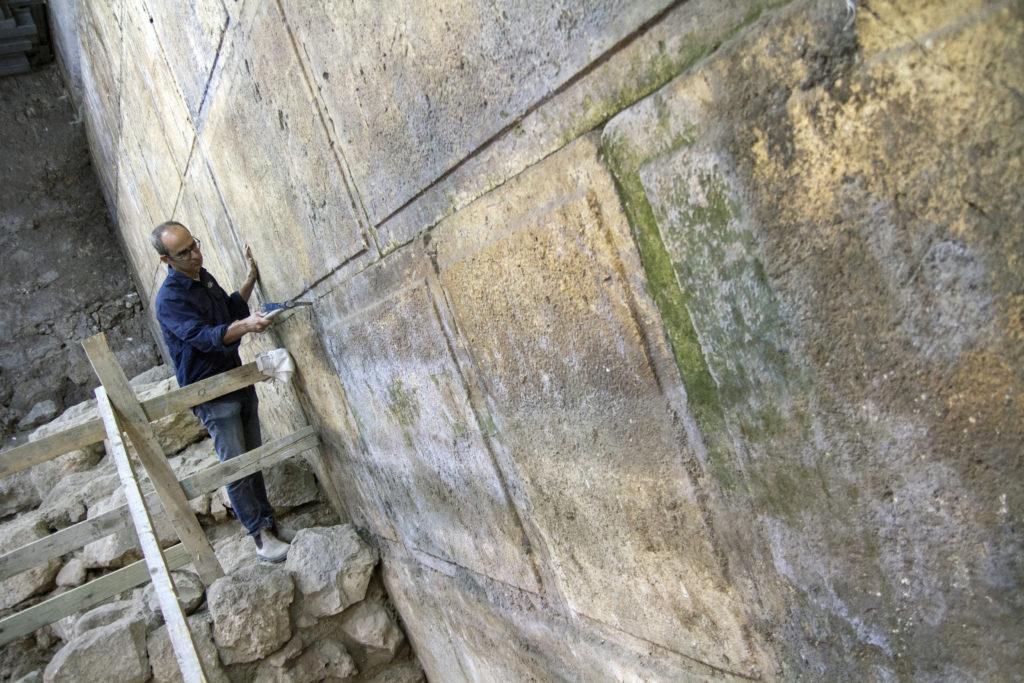 """ארכיאולוג רשות העתיקות ד""""ר ג'ו עוזיאל רשות העתיקות ליד אבני הכותל שנחשפו בחפירה. צילום: יניב ברמן"""