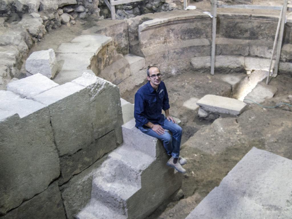 """ד""""ר ג'ו עוזיאל מרשות העתיקות יושב על מדרגות מבנה התיאטרון. צילום: יניב ברמן"""