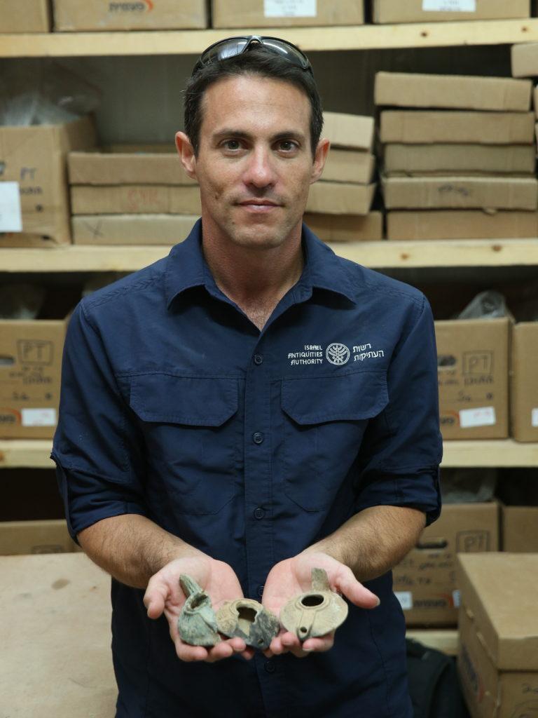 נחשון זנטון מנהל החפירה ברחוב המדורג מטעם רשות העתיקות, מחזיק נרות חרס מהתקופה העבאסית שנמצאו בבור האשפה