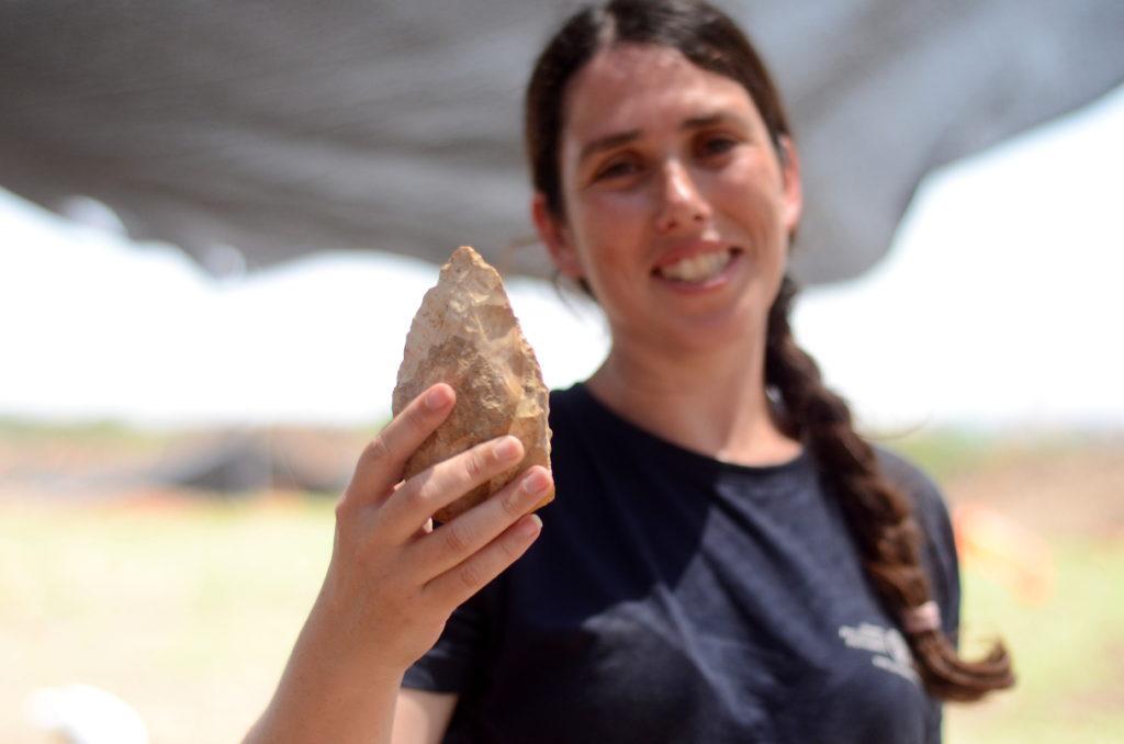 מעין שמר, מנהלת החפירה מטעם רשות העתיקות, מציגה אבן יד בת חצי מליון שנה